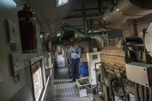 """巴基斯坦引进的""""绿线""""列车内部,车组人员在发动机旁工作。(彭博新闻社网站)"""