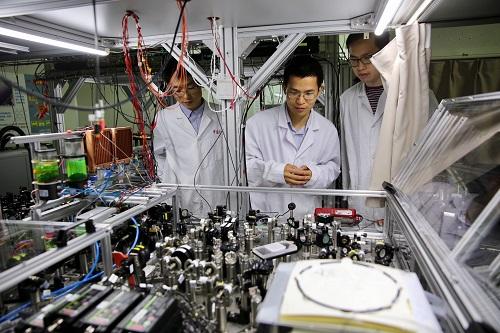 """资料图片:中国科学技术大学陆朝阳教授(中)和学生们在中科院量子信息和量子科技创新研究院上海实验室检查光量子计算机的运行情况(2017年5月3日摄)。量子物理学家潘建伟和他的学生陈宇翱、陆朝阳先后回国,三人三夺世界量子电子学和量子光学领域最高荣誉——菲涅尔奖。他们在回国后组建了一支中国物理界的""""梦之队""""。新华社记者 金立旺 摄"""