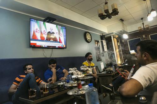 5月8日,在伊朗首都德黑兰,人们观看伊朗总统鲁哈尼的电视讲话。新华社发