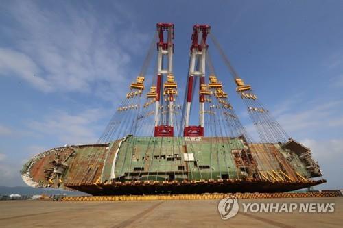 """5月10日,在木浦新港,""""世越""""号扶正工作即将启动,工作人员正在对船体进行检查。(韩联社)"""