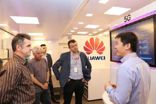 几位保加利亚客户在听华为工作人员介绍华为公司的5G网络技术。(新华社)