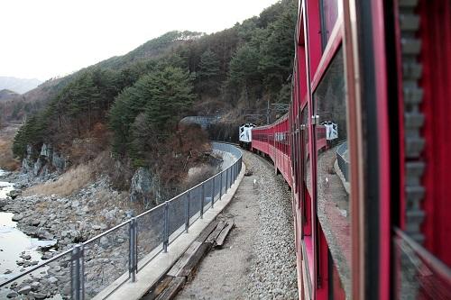 """韩国铁道公社往返于江原道铁岩与庆尚北道汾川之间的峡谷列车穿行在韩国""""白头大干""""山峡谷(2月3日摄)。新华社记者彭茜摄"""