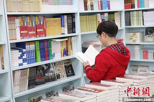资料图:一女子在某书店选购图书。 中新社记者 于琨 摄