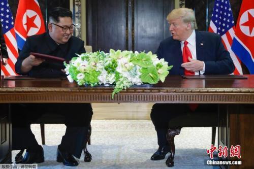 资料图片:金正恩与特朗普签署联合文件仪式现场。