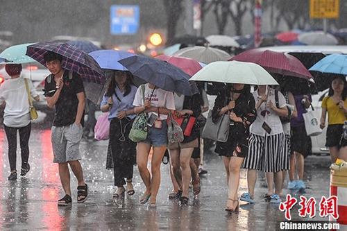 资料图:广州民众在暴雨中出行。 中新社记者 陈骥<span class=