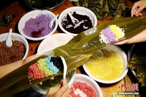 资料图:广西山区壮族同胞赶制五彩粽子迎端午。谭凯兴 摄