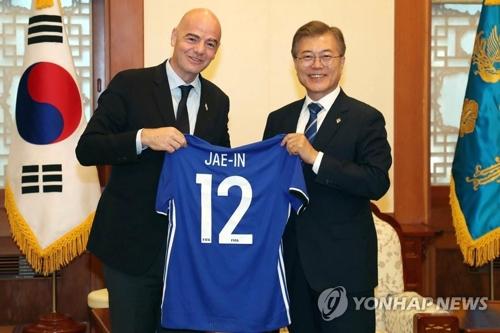 12日,文在寅接受国际足联主席因凡蒂诺赠送的队服,上面印有文在寅名字