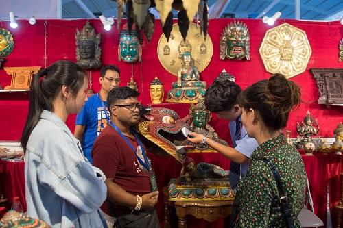 来自尼泊尔的客商(左三)在第5届中国-南亚博览会上出售特色手工艺品(2018年6月18日摄)。 新华社记者 胡超摄