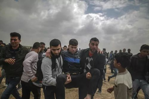 ▲资料图片:3月30日,在加沙地带边境,巴勒斯坦人转移一名受伤的示威者。