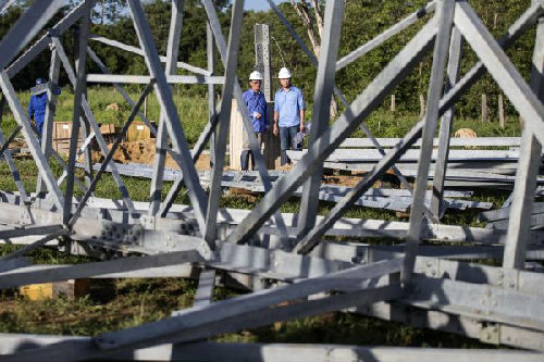 2月14日,在巴西纳雄耐尔港,山东电建一公司员工杨官辉(左)和武晓成在施工现场工作。彼时,巴西美丽山水电站特高压输电工程二期项目第五标段建设正在纳雄耐尔港有序进行。(新华社)