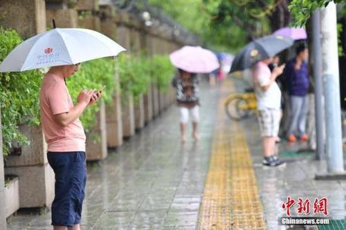 资料图:雨中出行的人们。 中新社记者 张浪 摄