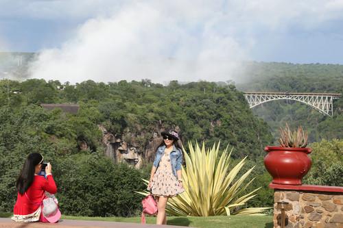 资料图片:2019-01-22,在津巴布韦维多利亚瀑布城,来自中国的一对母女以远处的赞比西铁桥为背景拍照留念。新华社发