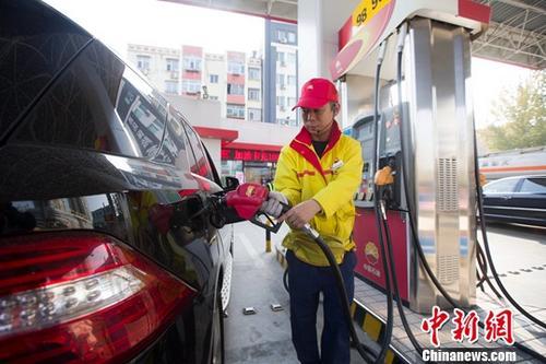 资料图:加油站内工作人员正在给车辆加油。中新社记者 张云 摄