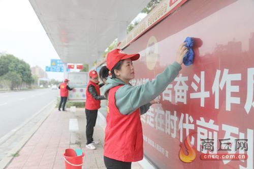 民权县财政局青年志愿者正在擦拭公交车站牌