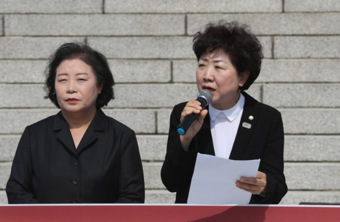11日,两名女政客参加剃收抗议止列(韩联社)