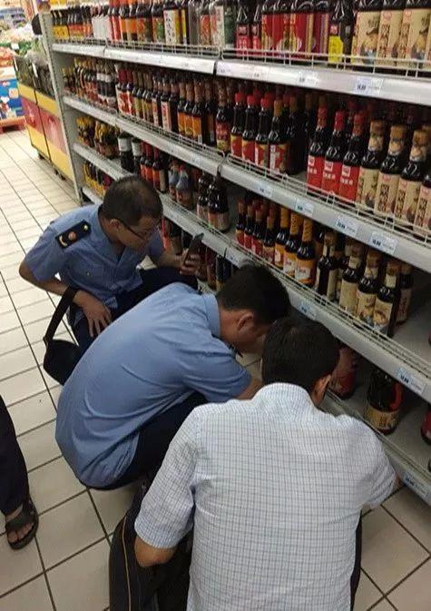 ▲执法人员在苏果超市检查加加酱油。洪敬谱/摄