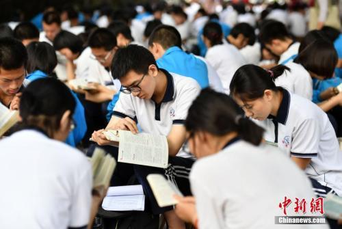 6月7日清晨,河北石家庄一高考点附近,参加高考的学生们利用进入考场前的时间看书复习。 中新社记者 翟羽佳 摄