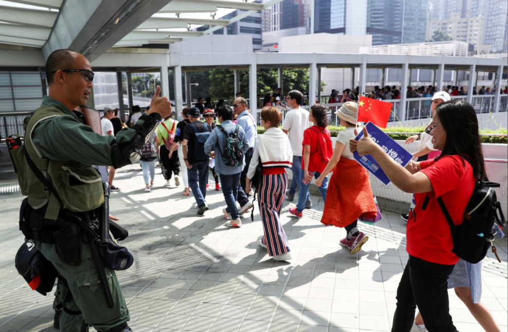 """香港市民自发上街""""撑警"""" ,英媒拍到警民偶遇时暖心一幕。(图源:路透社)"""