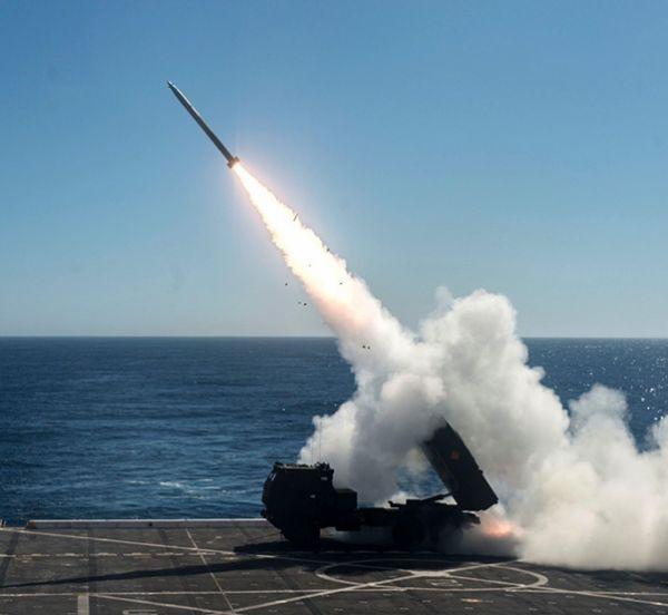 """資料圖片:美陸戰隊""""海馬斯""""遠火從船塢登陸艦上發射火箭彈瞬間。(圖片來源於網絡)"""