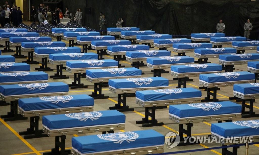 韩国举行的遗骸回国仪式上,棺材用联合国旗包裹。(韩联社)
