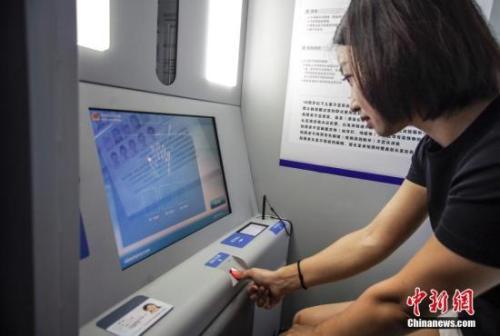 资料图:市民正在身份证办理自助设备前办理业务。中新社记者 贾天勇 摄