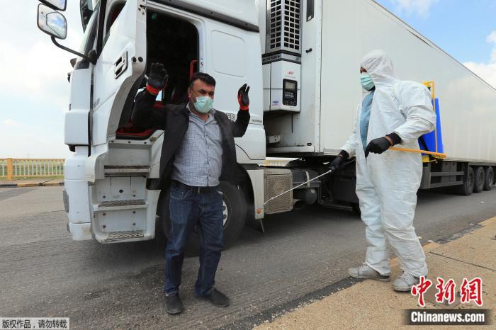 土耳其一名身穿防护服的工作人员,给戴口罩的驾驶员喷洒消毒水。