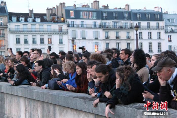 资料图:当地时间2019年4月15日晚,法国巴黎圣母院发生大火,引发民众高度关注,众多民众在现场附近聚集。中新社记者 李洋 摄