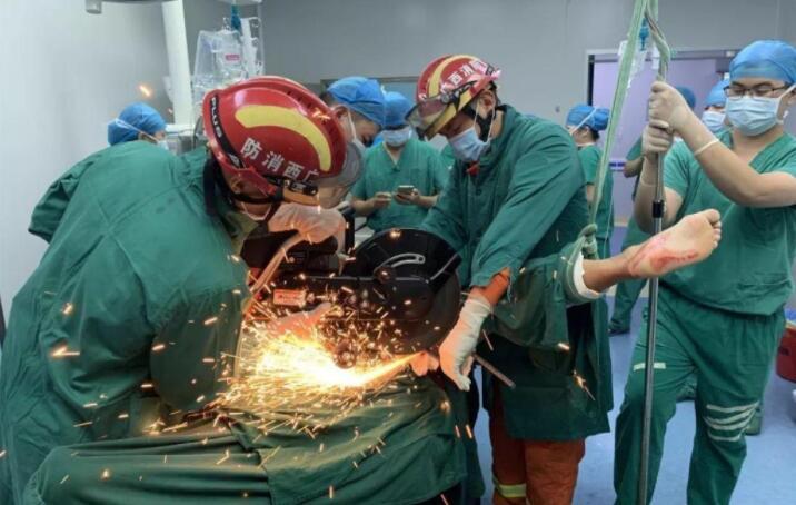 消防人员在手术台上将伤者体外的钢筋切断。