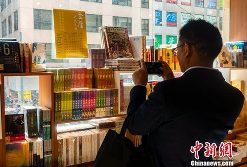 10月31日,在香港湾仔三联书店,一位顾客正在金庸作品专柜前拍照留念。10月30日,武侠小说泰斗查良镛(笔名金庸)在香港逝世,享年94岁。中新社记者 张炜 摄