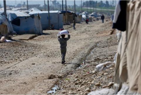 2019年3月6日,在伊拉克北部摩苏尔东南约30公里外的塞莱米耶1号安置营地,一名儿童搬运领取的救济粮。新华社发
