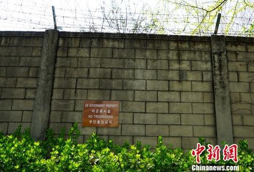 """图为驻韩好军基天中墙,稀布铁蒺藜并吊挂着""""制止进进""""的标牌。中新社记者 曾鼐 摄"""