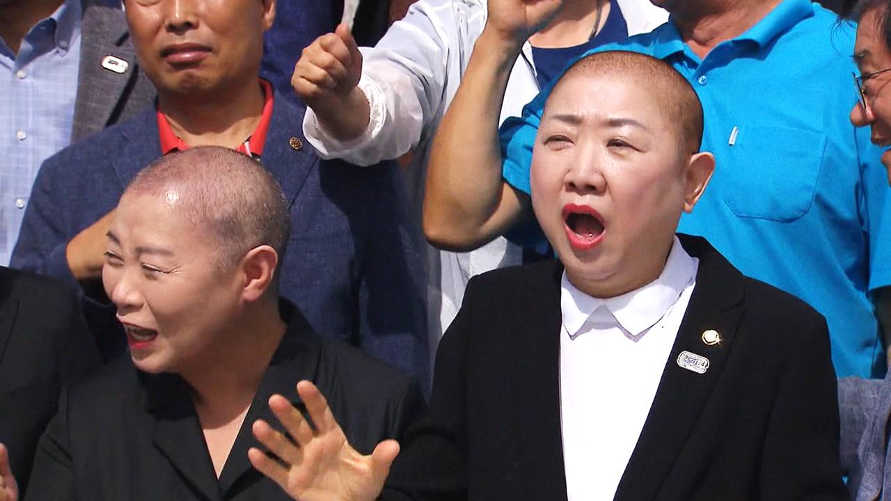剃收后,两人喊标语,请求文正在寅报歉(韩联社)