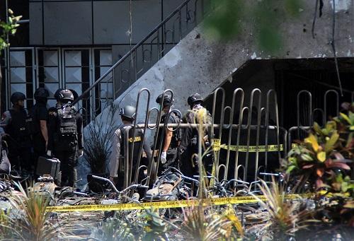 5月13日,在印度尼西亚东爪哇省泗水市,安全人员聚集在爆炸现场。新华社发(库尔尼亚万摄)