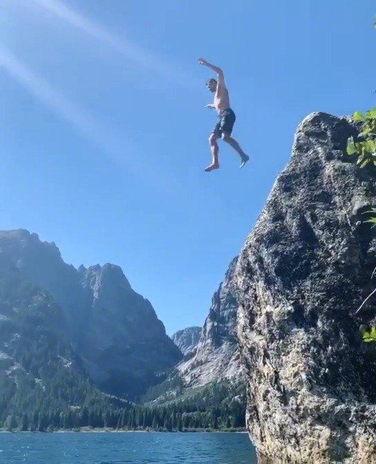 度假中的乐福来到怀俄明州享受大自然美景,站在悬崖上
