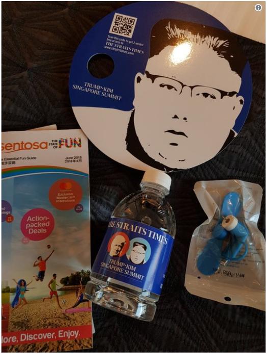 新加坡方面为记者们准备的礼品袋内含一把扇子、一个迷你电风扇、一瓶水和一份旅行指南。