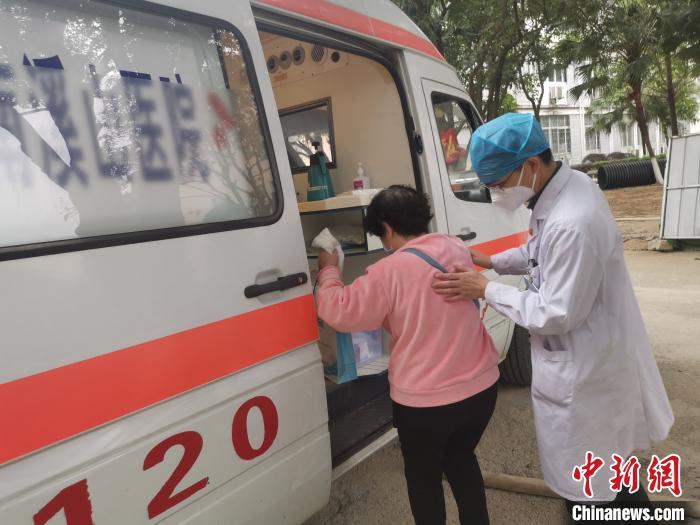 图为医护人员搀扶病友刘阿姨上车离开医院。 张超群 摄
