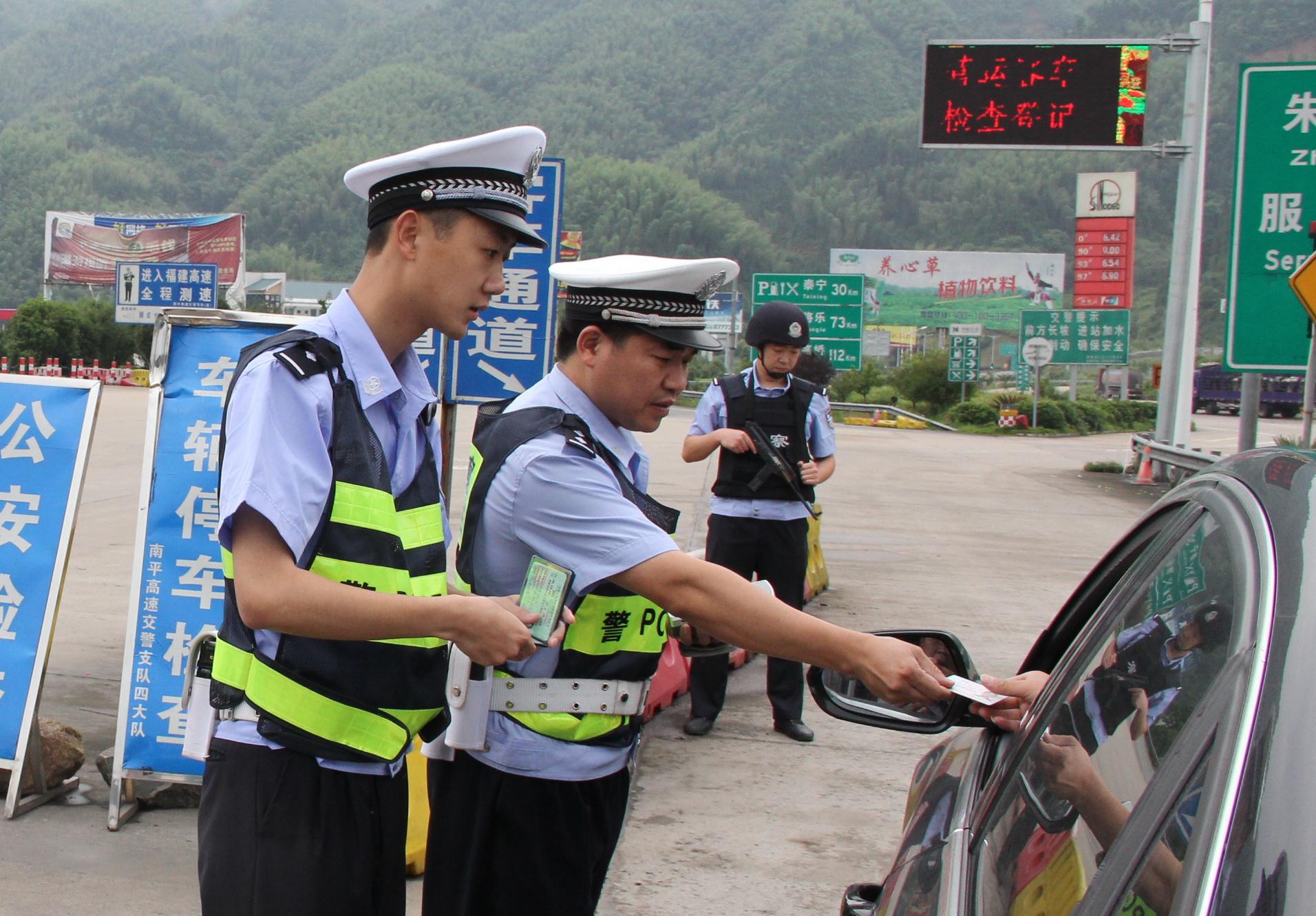 2014年6月,刘才添与同事俞有忠在福银高速闽赣省际收费站检查过往车辆证件。李嘉 摄
