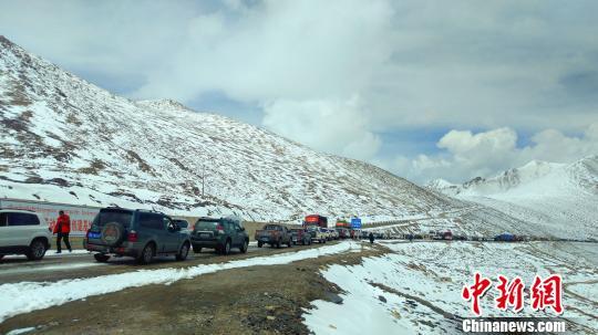 武警某部交通三支队驻左贡县中队官兵向结冰路面抛撒工业盐 路凯 摄 救援中