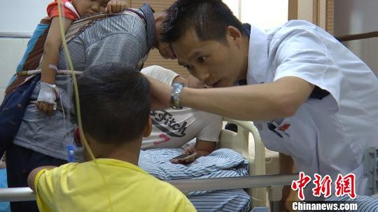 图为医生在给中毒的孩子进行检查。 孔金花 摄