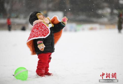 资料图:2月12日,北京迎来今冬第二场降雪,一名幼童仰头感受雪花纷飞。中新社记者 赵隽 摄