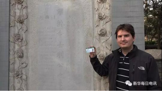 清华大学留学生西泰拿出带有自己名字的学生证与利玛窦墓碑合影。