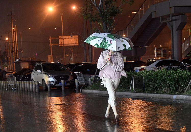 15时52分,广渠路,行人打伞雨中疾行。
