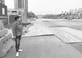 女子雨天骑车摔在施工路的铁板上