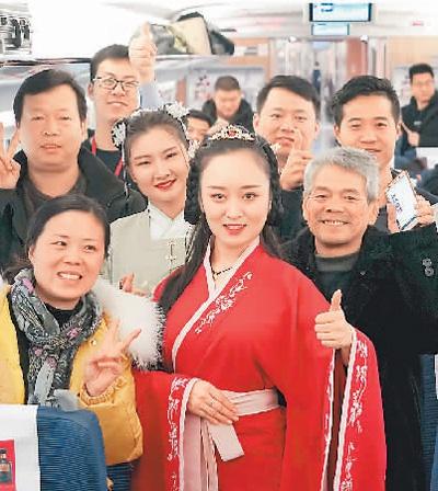 在由郑州东站至襄阳东站的G4051次列车上,身穿汉服的郑州客运段工作人员与乘客合影。新华社记者 李 安摄