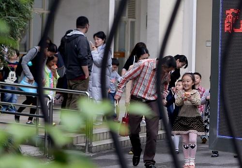 资料图片:2015年5月9日,在上海市一民办小学门口,小朋友和家长参加完招生面谈,走出学校。新华社记者 刘颖 摄