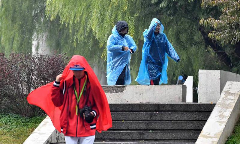 奥体中间,止人脱上了雨衣出止。