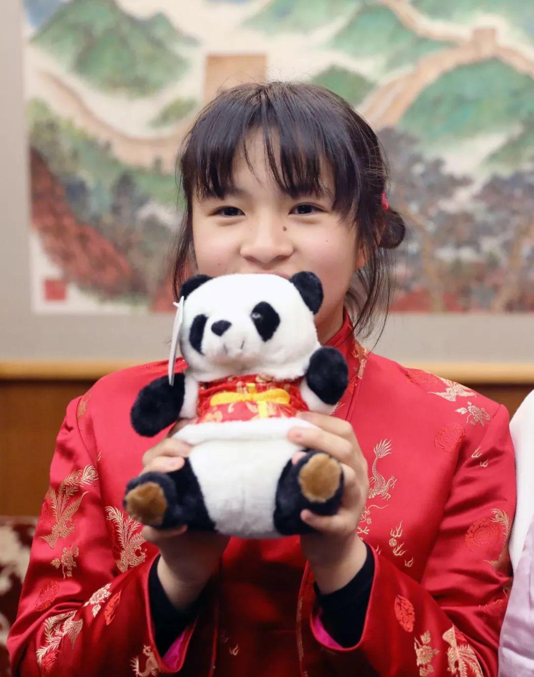 2月13日,旗袍女孩接受记者采访时一直抱着大熊猫玩偶不撒手。新华社记者 杜潇逸 摄