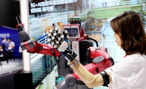 """2018年6月27日,""""2018世界移动大会-上海""""在沪开幕,工作人员在现场进行5G+AI(人工智能)技术的远程操作技术展示。 新华社记者 方喆 摄"""