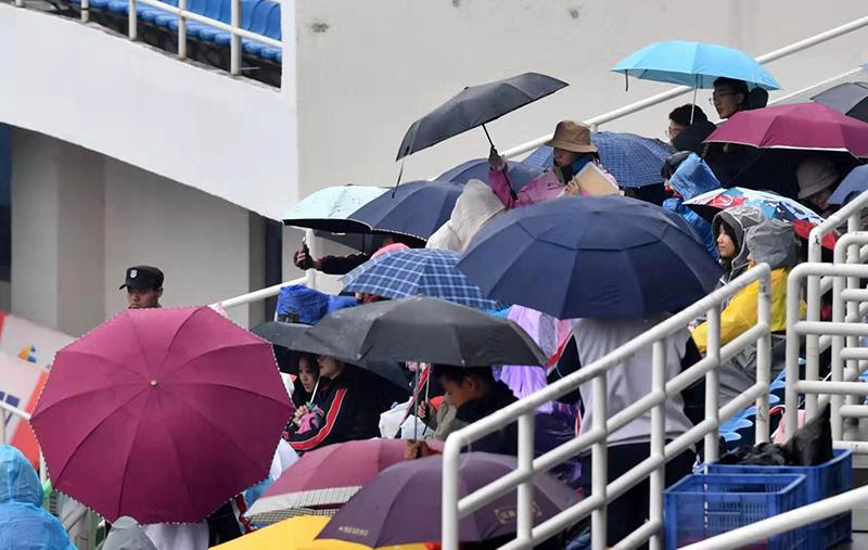 奥体中间看台,撑伞的不雅寡正在旁观角逐。