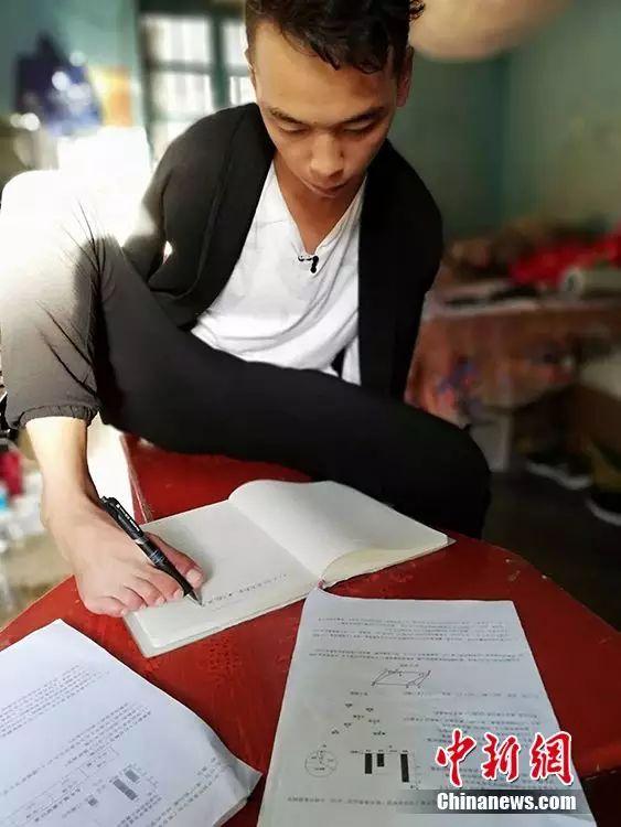 哥哥吴建早用脚写字。巧家县第三中学老师供图